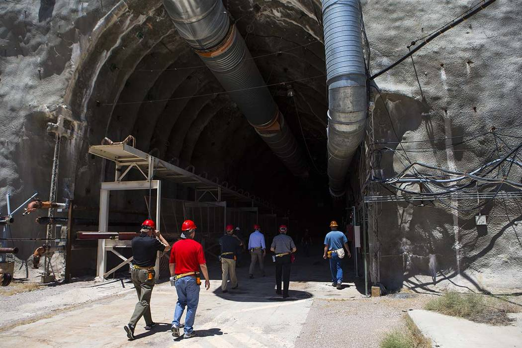 Members of a congressional tour make their way through the north portal of Yucca Mountain near ...