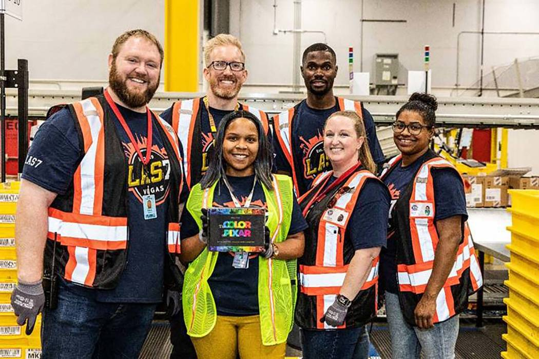 Amazon team members show off the first item received into the new North Las Vegas facility: a h ...