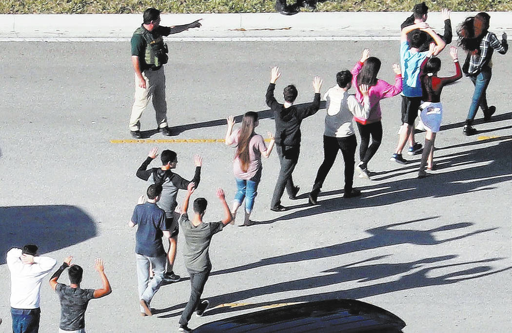 Students hold their hands in the air as they are evacuated by police from Marjorie Stoneman Dou ...