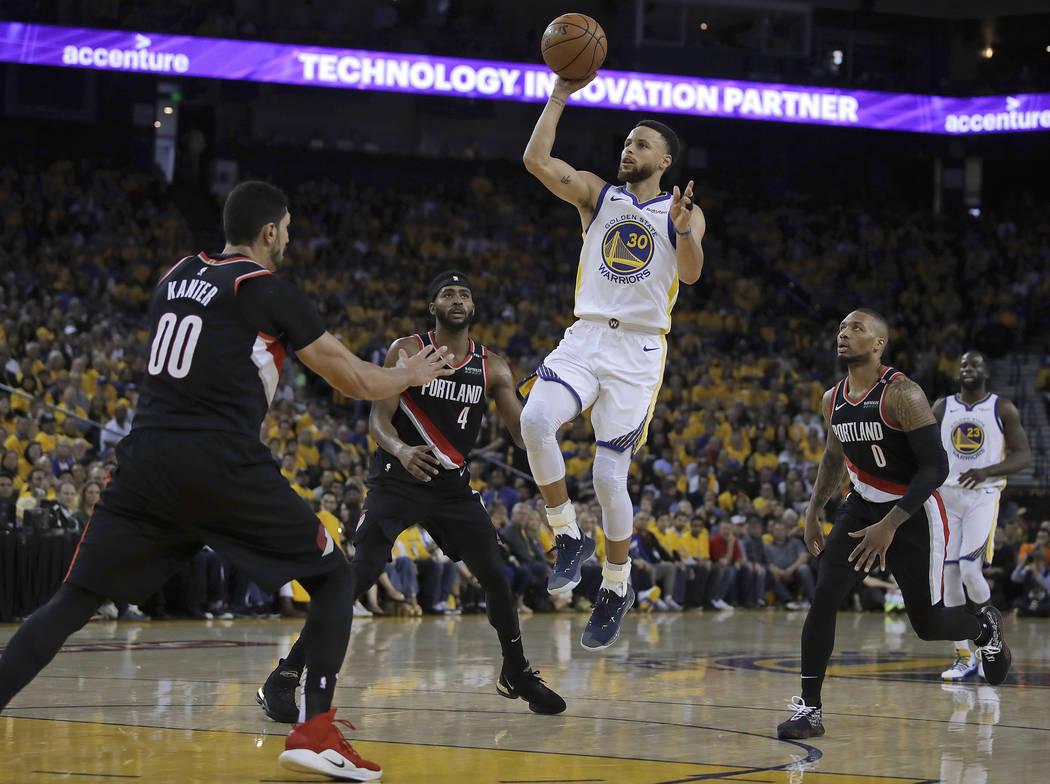 Golden State Warriors' Stephen Curry (30) shoots between Portland Trail Blazers' Maurice Harkle ...