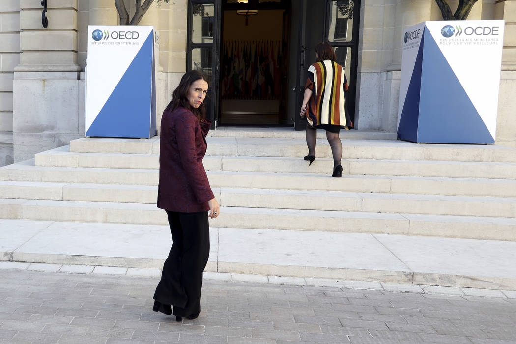 New Zealand Prime Minister Jacinda Ardern, left, leaves after a press conference, at the OECD h ...
