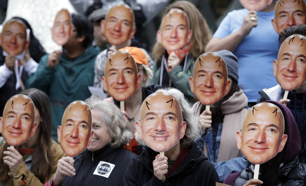 FILE - In this Oct. 31, 2018, file photo, demonstrators hold images of Amazon CEO Jeff Bezos ne ...