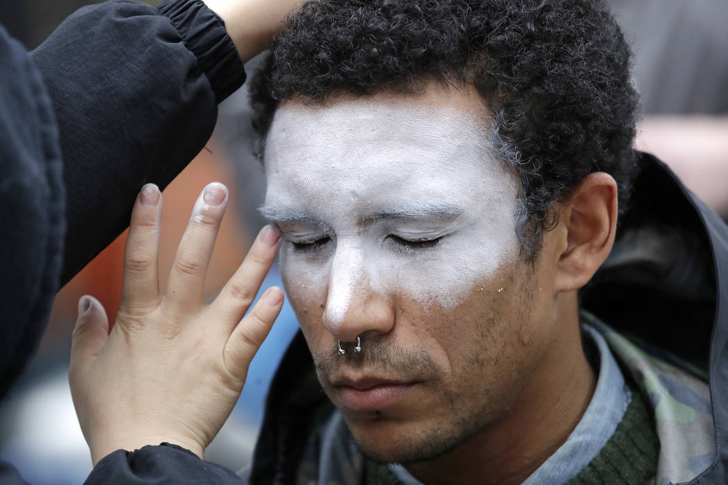 A man, who declined to be identified, has his face painted to represent efforts to defeat facia ...