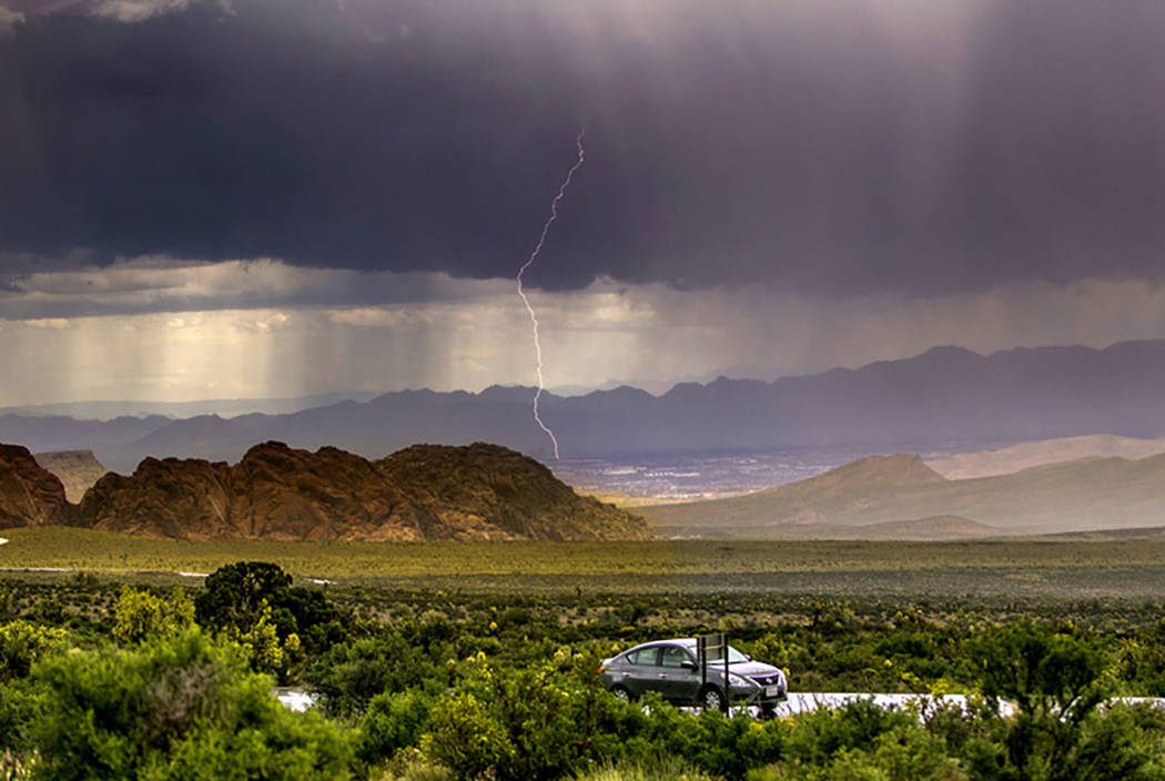 A lightning bolt streaks down as a fast-moving storm makes its way through the Red Rock Canyon ...