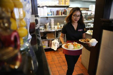 Lita Harris runs food to customers during lunch at Archi's Thai Bistro in Las Vegas, Thursday, ...