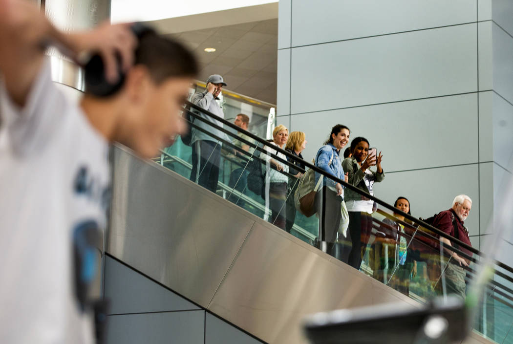 Travelers arrive as DJ Play performs for them including EDC visitors coming through Terminal 3 ...