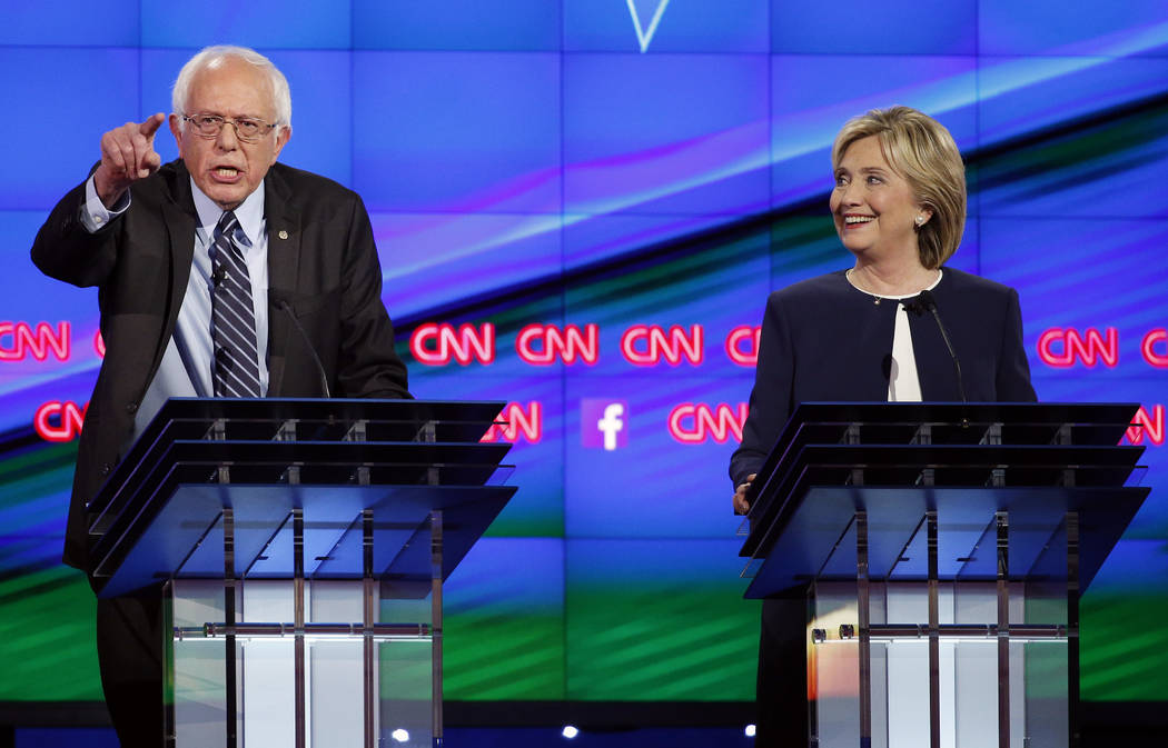 In this Tuesday, Oct. 13, 2015, file photo, Sen. Bernie Sanders, of Vermont, left, speaks as Hi ...