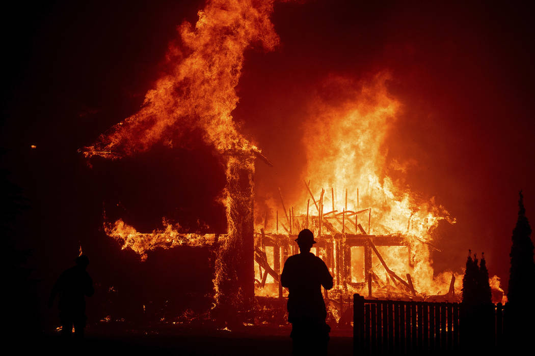 In this Thursday, Nov. 8, 2018 file photo, a home burns as the Camp Fire rages through Paradise ...