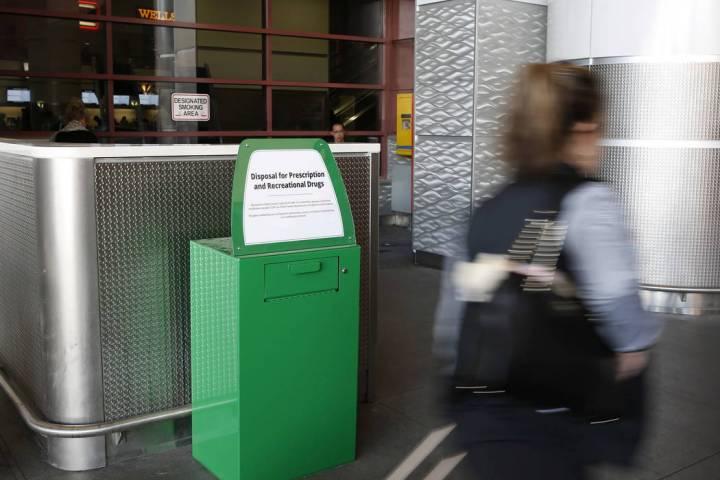 A passenger walks past a recently installed marijuana amnesty drop box at McCarran Internationa ...