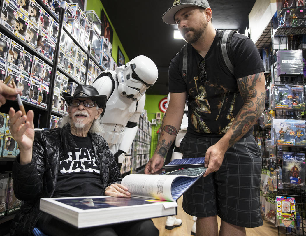 Colin Cantwell, left, concept artist and model builder for the original Star Wars movies, signs ...