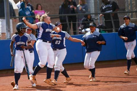 Shadow Ridge players celebrate a home run by Caitlin Covington, not pictured, during the second ...