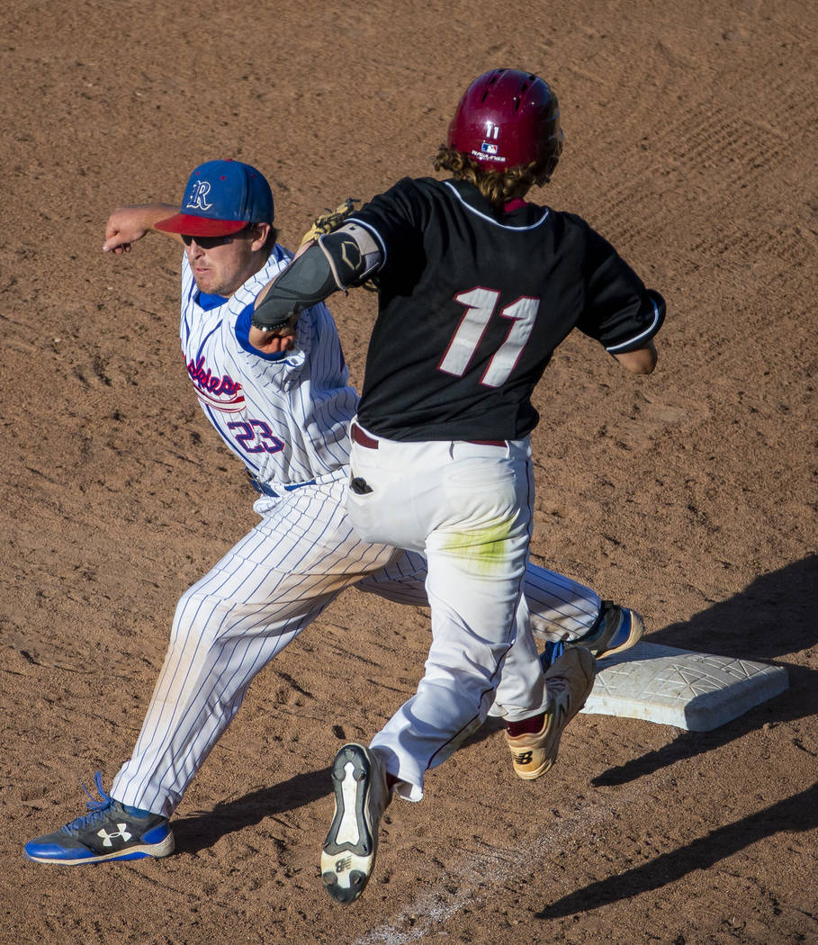 Reno's Ryan Hess (23) attempts a tag on Desert Oasis runner Josh Sharman (11) but will bobble t ...