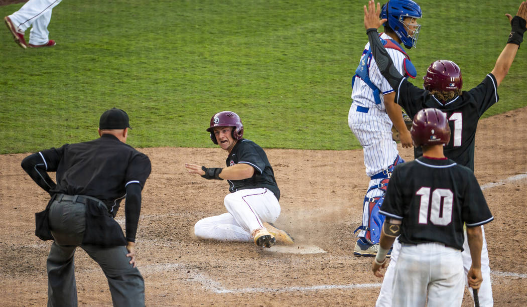 Desert Oasis' Colton Zobrist (7) slides in safely for another run over Reno during their Class ...