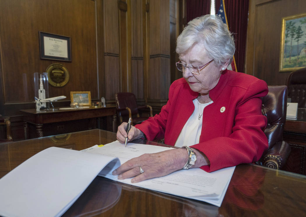 This photograph released by the state shows Alabama Gov. Kay Ivey signing a bill that virtually ...