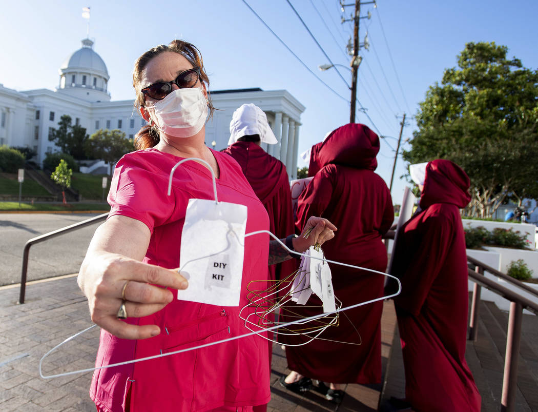 Laura Stiller hands out coat hangers as she talks about illegal abortions during a rally agains ...