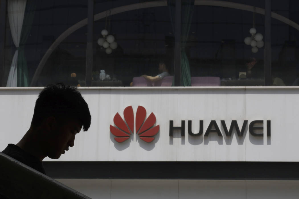 A Chinese man is silhouetted near the Huawei logo in Beijing on Thursday, May 16, 2019. In a fa ...