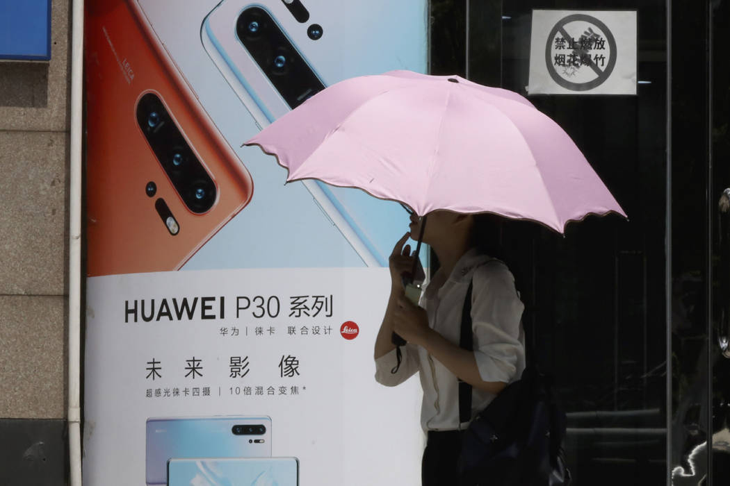 A woman walks past advertisement for Huawei smartphones in Beijing on Thursday, May 16, 2019. I ...