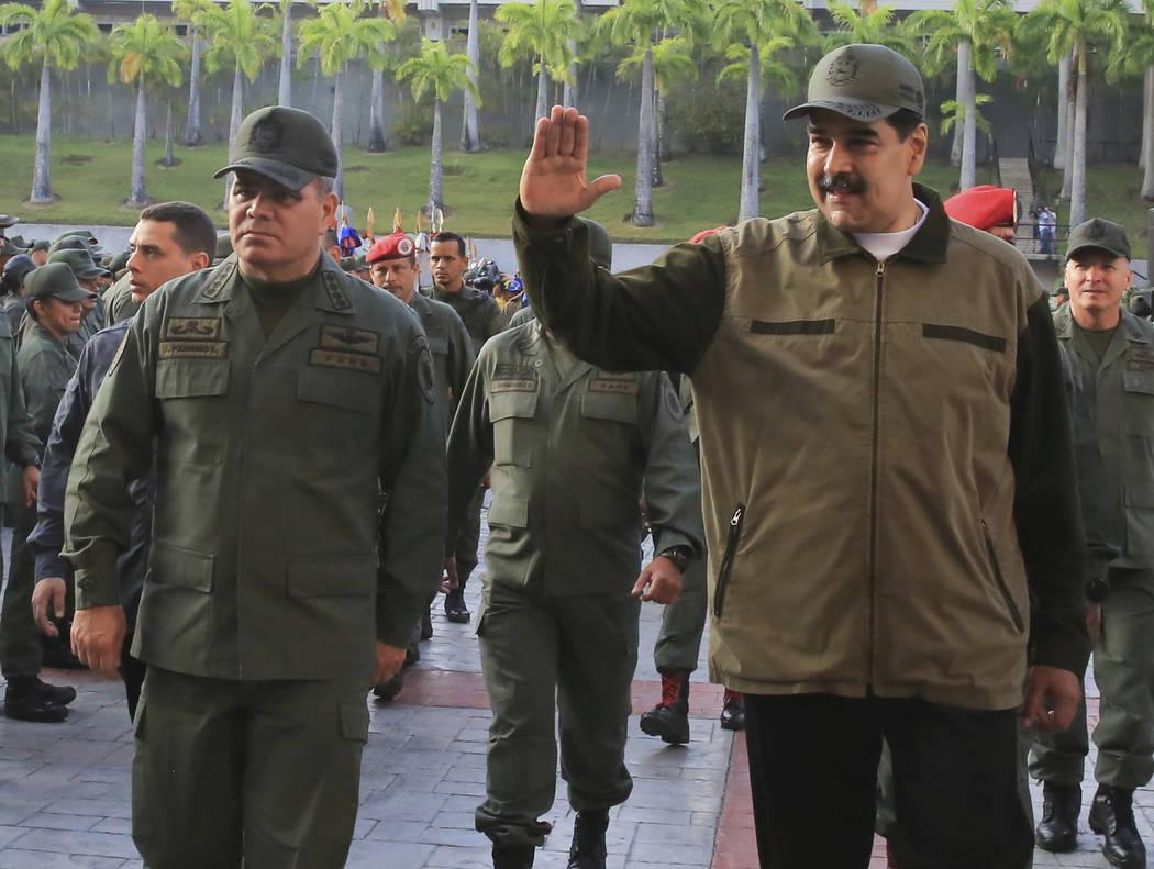 In this photo released by Miraflores Press Office, Venezuela's President Nicolas Maduro, right, ...