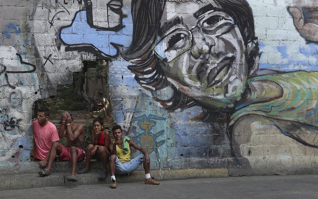 A group of young people rest in a hole in the wall at the Agua Salud neighborhood of Caracas, V ...
