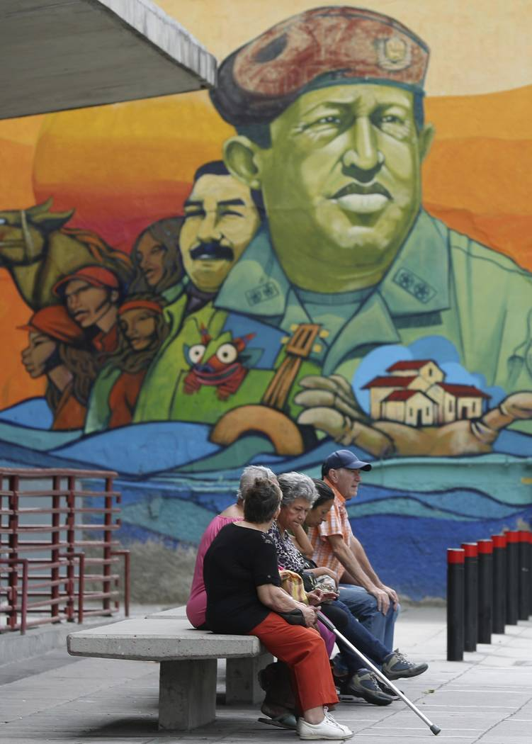 Residents rest on a bench backdropped by a mural featuring Venezuela's late President Hugo Chav ...