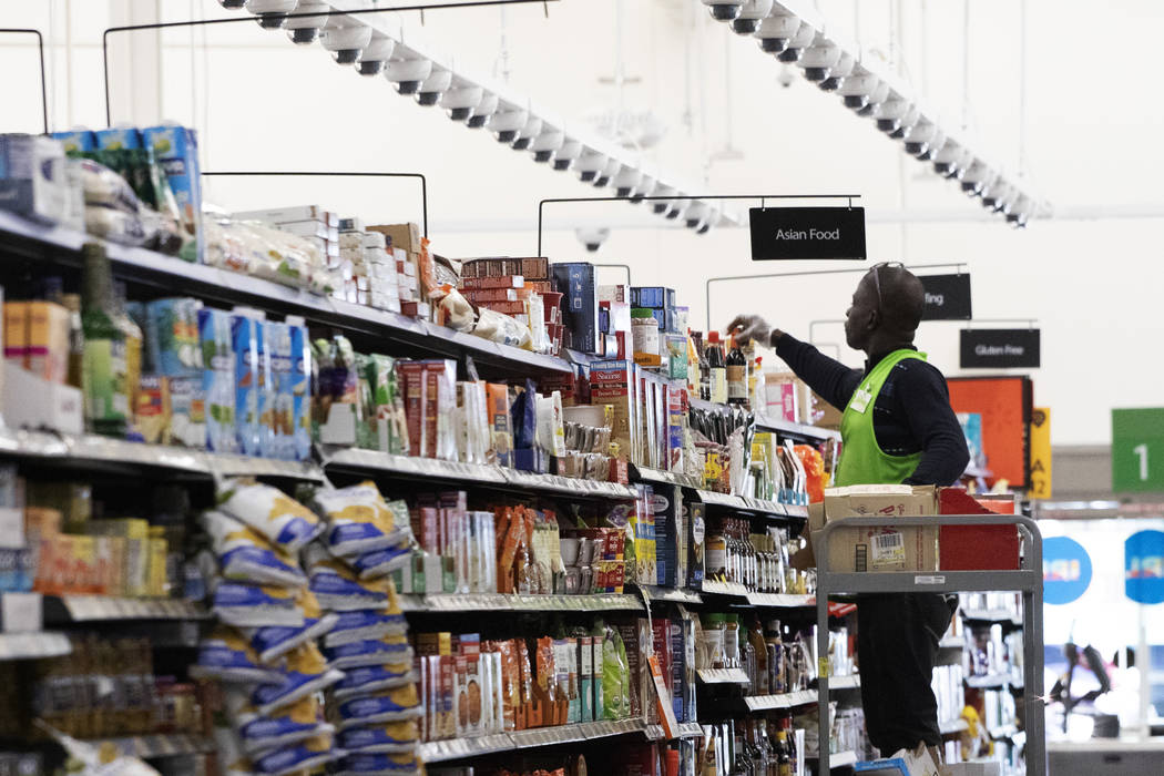 FILE - In this April 24, 2019, file photo a Walmart associate arranges items on a shelf at a Wa ...
