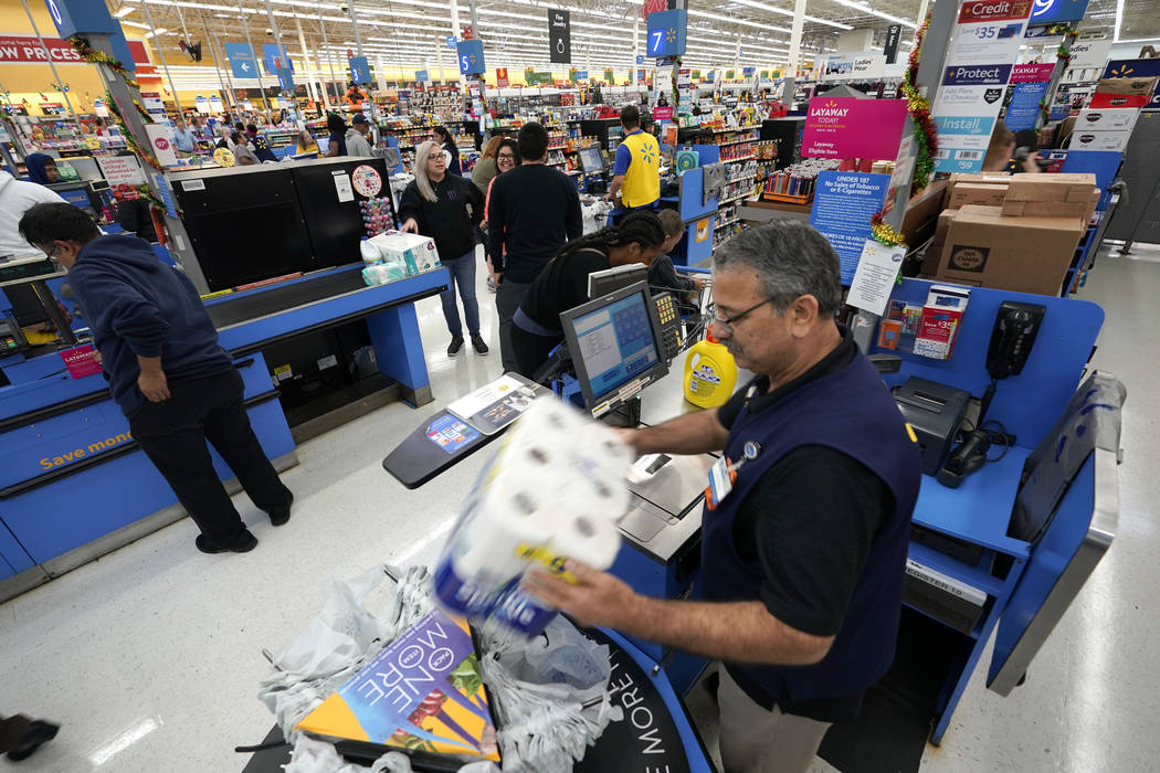 FILE - In this Nov. 9, 2018, file photo Walmart associate Javaid Vohar, right, checks out custo ...