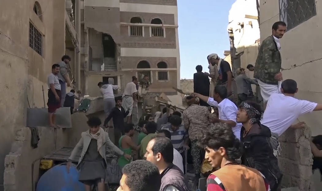 In this frame grab from from video, people search in the rubble following Saudi-led coalition a ...