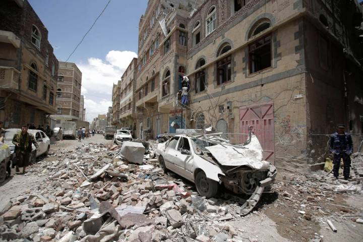 People inspect the site of an airstrike by Saudi-led coalition in Sanaa, Yemen, Thursday, May, ...