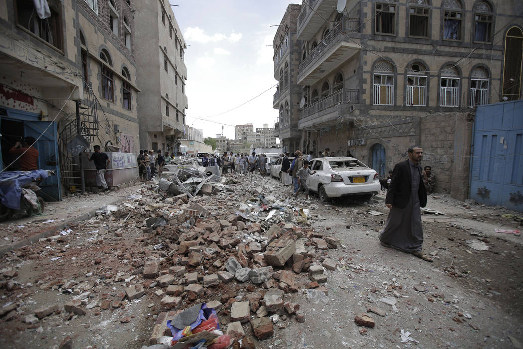 People inspect the site of an airstrike by Saudi-led coalition forces, in Sanaa, Yemen, Thursda ...