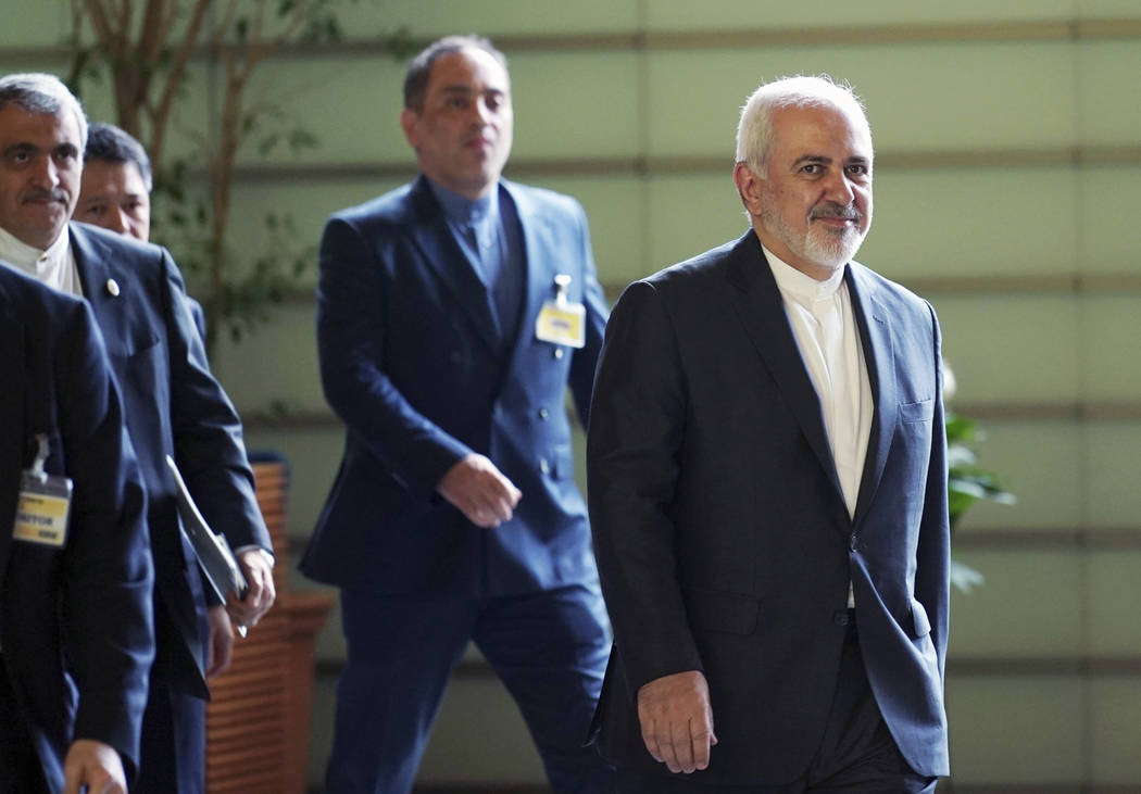 Iranian Foreign Minister Mohammad Javad Zarif, right, walks to meet Japanese Prime Minister Shi ...