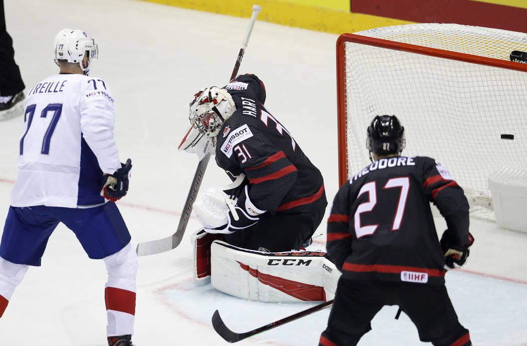 Canada's Shea Theodore, right, and Sacha Treille of France, left, watch as Canada's goaltender ...