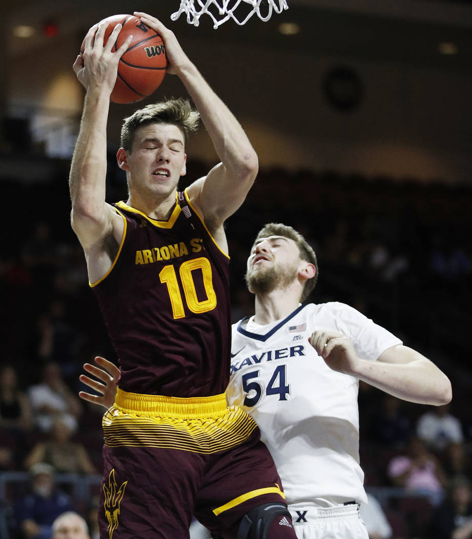 Arizona State's Vitaliy Shibel grabs a rebound over Xavier's Sean O'Mara during the first half ...