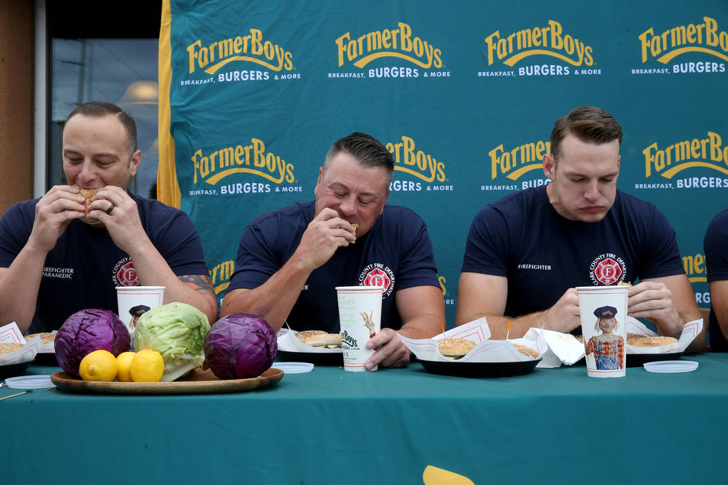 Clark County firefighters from left, Shawn Goldberg, Erik Oliver and Shane Salmon compete again ...