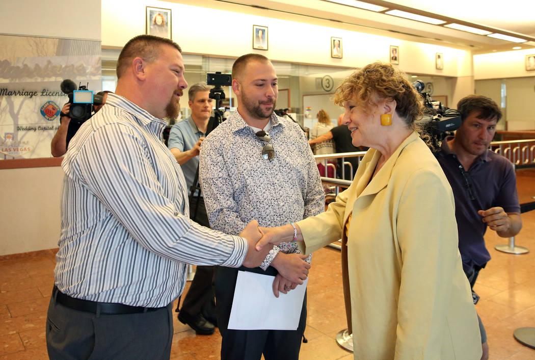 County Clerk Lynn Goya, right, congratulates James Johnson, left, and his partner, Matthew Tipp ...