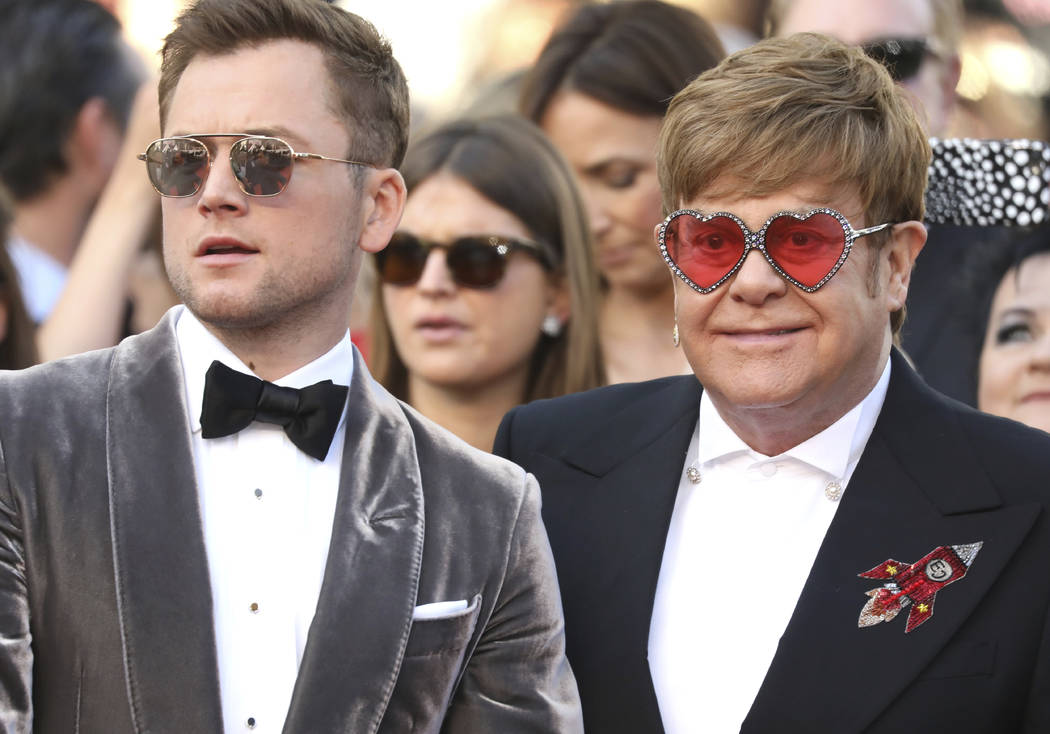 Actor Taron Egerton, left, and singer Elton John pose for photographers upon arrival at the pre ...