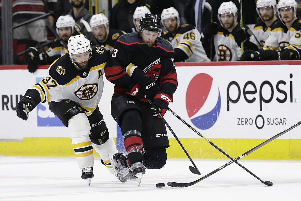 Boston Bruins' Patrice Bergeron (37) reaches in on Carolina Hurricanes' Warren Foegele (13) dur ...