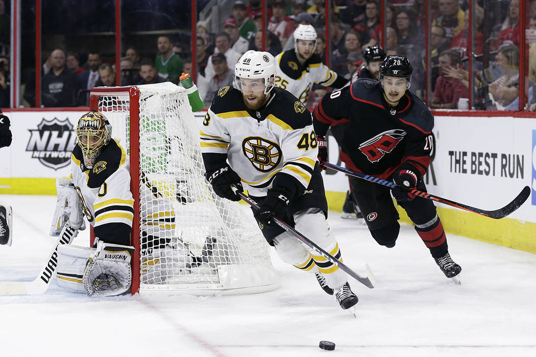 Boston Bruins' Matt Grzelcyk (48) controls the puck against a chasing Carolina Hurricanes' Seba ...