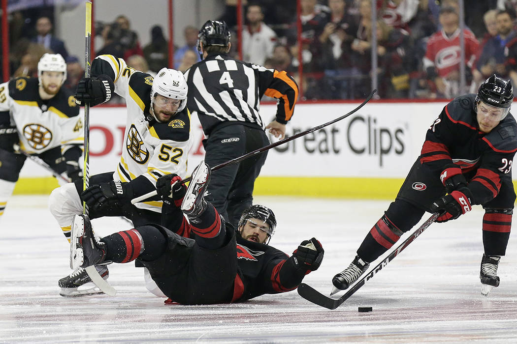 Boston Bruins' Sean Kuraly (52) and Carolina Hurricanes' Greg McKegg struggle during a face-off ...