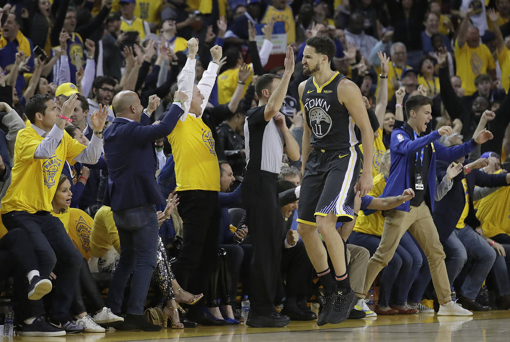 Golden State Warriors guard Klay Thompson (11) celebrates with fans after scoring against the P ...