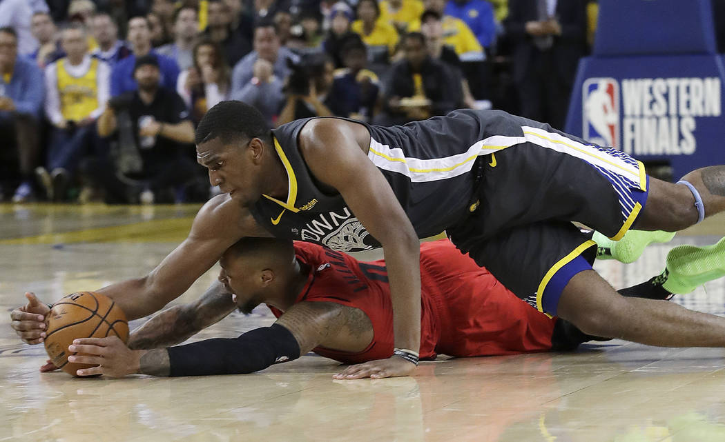 Golden State Warriors center Kevon Looney, top, reaches for the ball over Portland Trail Blazer ...
