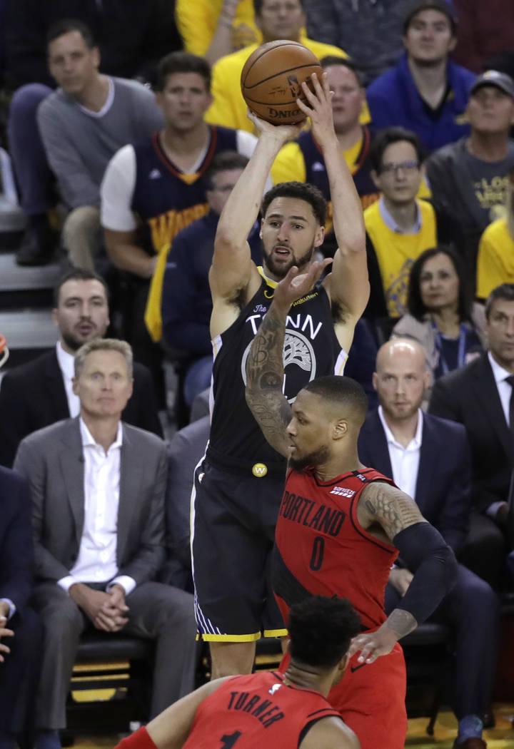 Golden State Warriors' Klay Thompson shoots over Portland Trail Blazers' Damian Lillard (0) dur ...