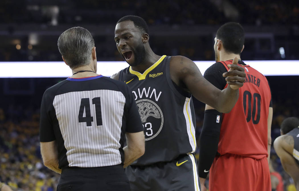 Golden State Warriors forward Draymond Green gestures while talking with referee Ken Mauer (41) ...
