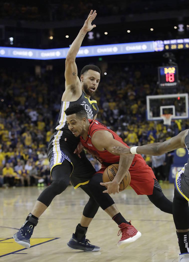 Portland Trail Blazers guard CJ McCollum, right, drives against Golden State Warriors guard Ste ...