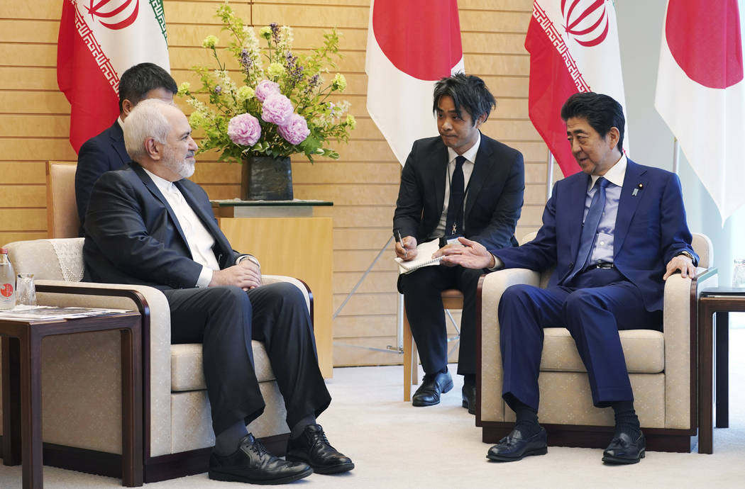 Iranian Foreign Minister Mohammad Javad Zarif, left, and Japanese Prime Minister Shinzo Abe, ri ...