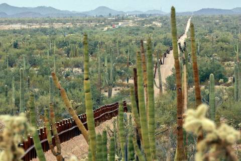 A fence separating Organ Pipe Cactus National Monument, right, and Sonyota, Mexico, is seen run ...