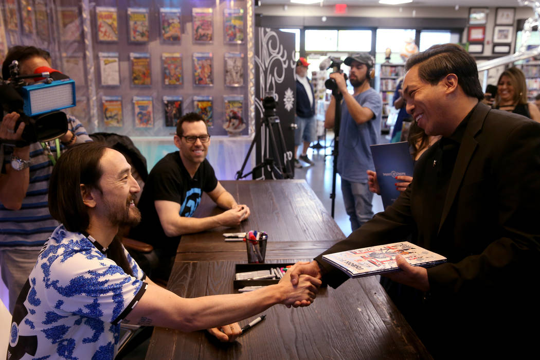 DJ Steve Aoki, left, greets Jasper Gonzales of Las Vegas during a signing for his new comic boo ...
