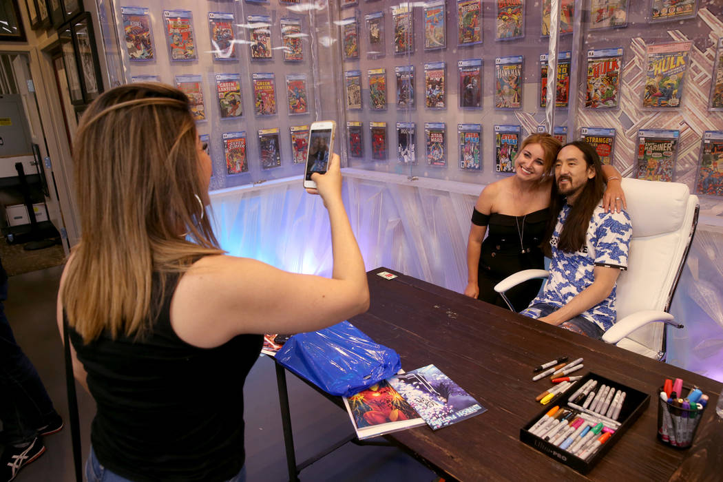 DJ Steve Aoki poses with Savannah Ward as Ada Fino takes a photo during a signing for his new c ...