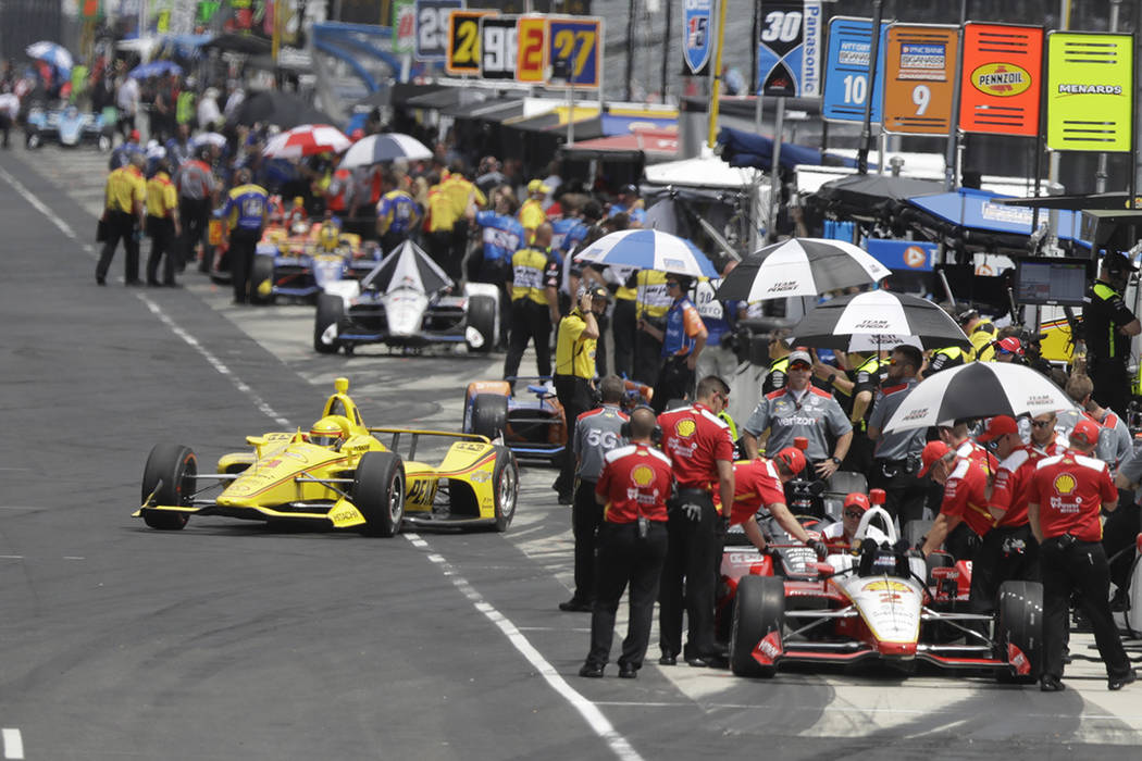 Helio Castroneves, of Brazil, pulls out of the pits during practice for the Indianapolis 500 In ...