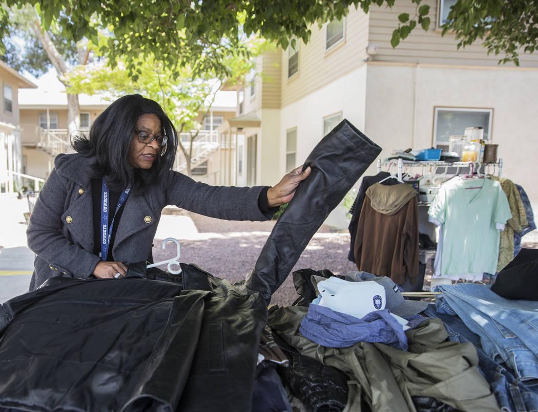 Melody Shay, property manger for Desert Plaza Senior Apartments, organizes clothing at a commun ...