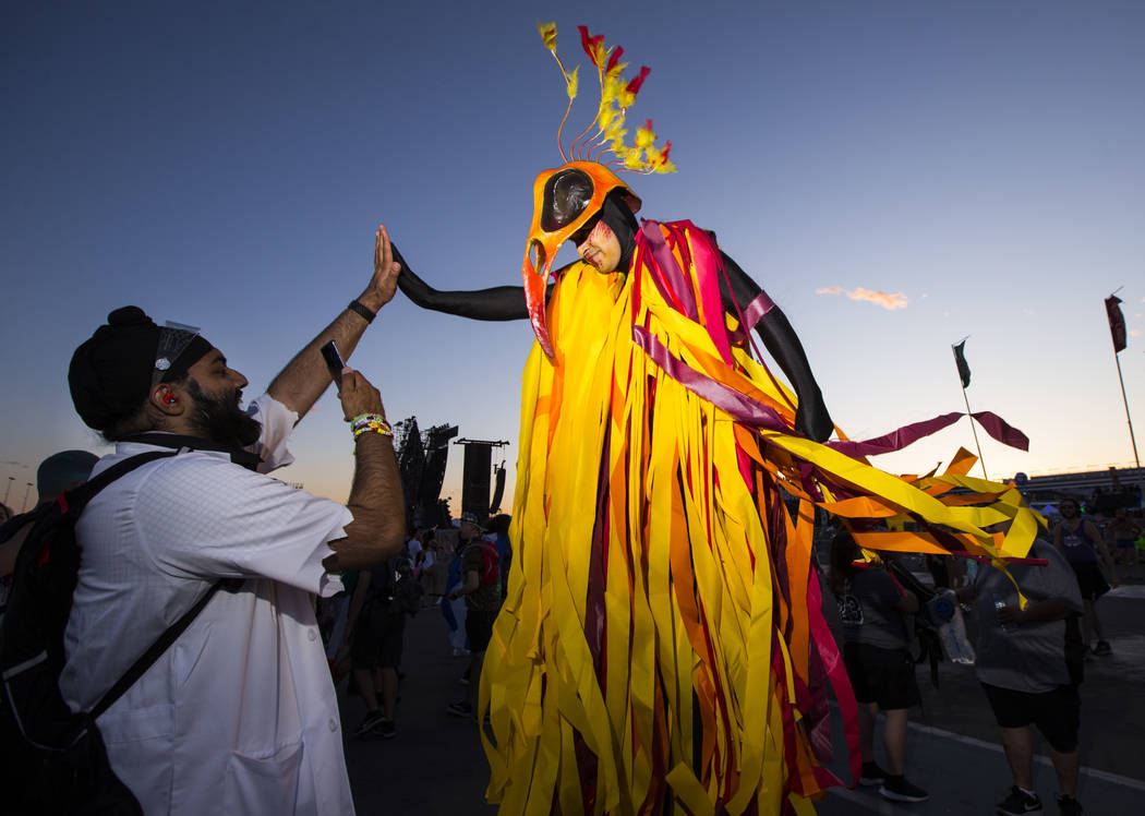 Hardeep Singh, of San Francisco, left, high-fives a costumed performer during the first day of ...